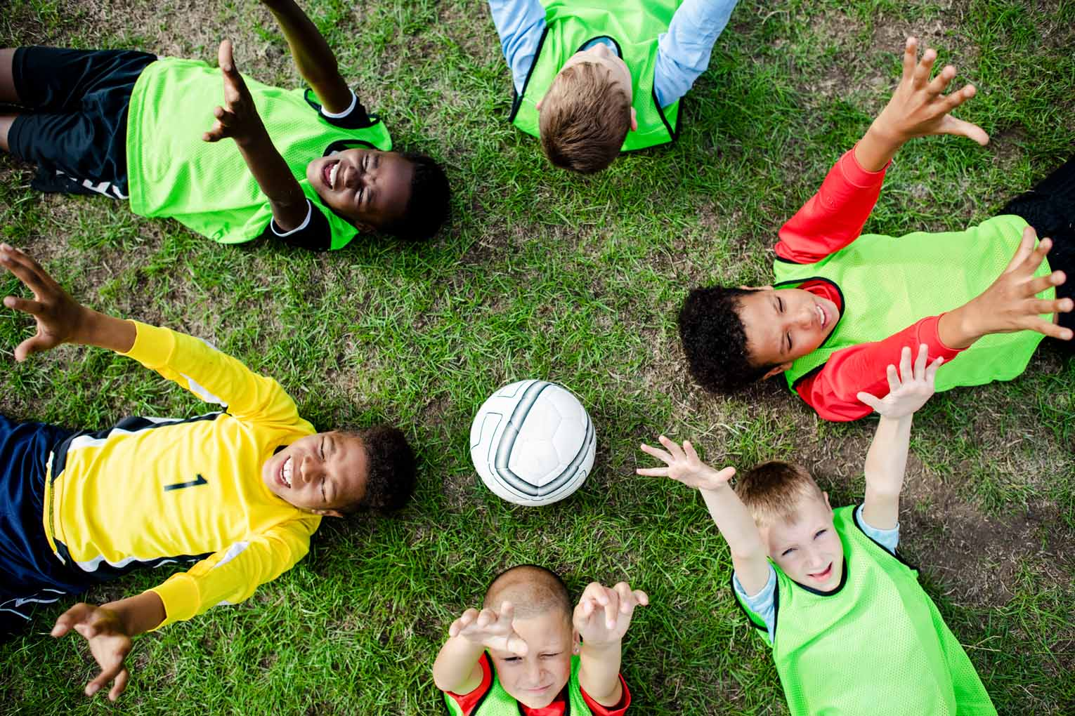 Junior football team lying around a football